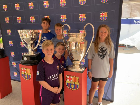 Noah Boehms, Andrew Boehms, Jason Kekenezi, Vinnie Spada and Myra Whitley have their picture taken with the Champions League trophy outside Michigan Stadium Saturday.