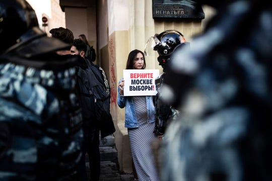"""A woman holds a poster reading """"Give us back our elections in Moscow!"""" in front of police during a protest in Moscow, Russia, Saturday, Aug. 10, 2019."""