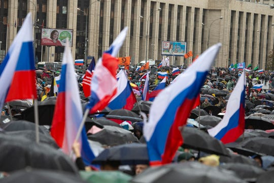 People with national flags stand under their umbrellas during a protest in Moscow, Russia, Saturday, Aug. 10, 2019.