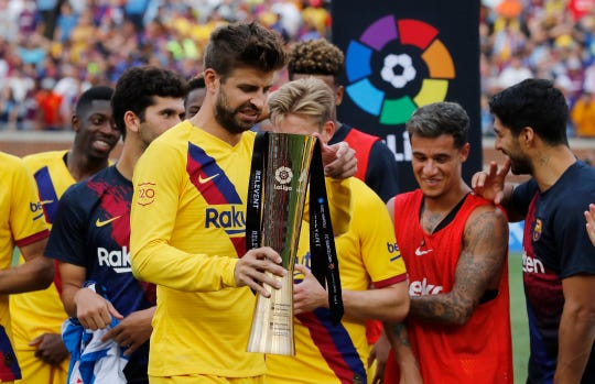 Barcelona defender Gerard Pique holds the winning team's trophy after a soccer match against Napoli. Barcelona defeated Napoli, 4-0.