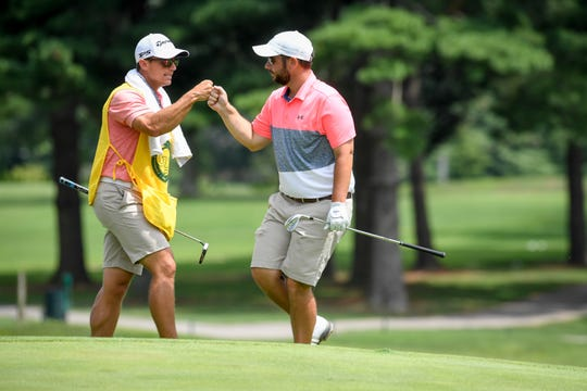 Brennan Phillips (right) fists bumps his caddy, Rob Phillips, his brother, during the Courier & Press Men's City golf tournament last August at Rolling Hills Country Club.