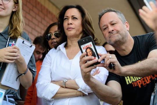 U.S. Sen. Kamala Harris, D-Cali., center, a 2020 democratic presidential candidate, listens to her introduction before walking onto the Des Moines Register Political Soapbox to give a stump speech to a packed crowd at the Iowa State Fair in Des Moines, Iowa, Saturday, Aug. 10, 2019.