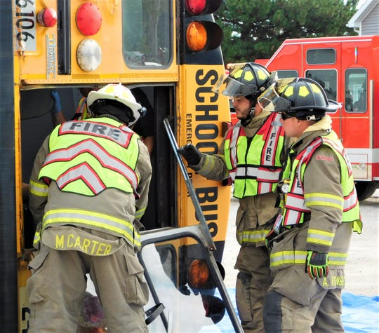 Green Springs Volunteer firefighters check on children through the back emergency door of a Clyde-Green Springs school bus during an joint drill.