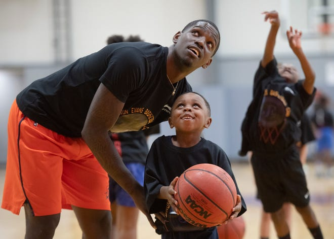 Jawun Evans lifts Patrick Neeley, 5, to take a shot at the hoop during the Jawun Evans Basketball Camp held at Legacy Early College Saturday, August 10, 2019.