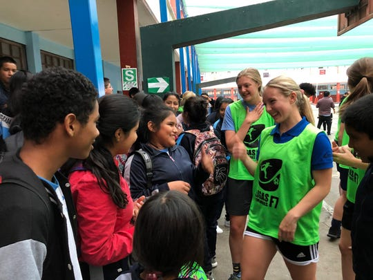 Lizzie Thompson, of Great Falls, in background in green, greets school children in Peru. A delegation of soccer players from the University of Montana's Mansfield Center took a trip to the South American country with the U.S. State Department as part of a cultural exchange.