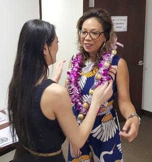 Hannah Cho Iriarte, Guam Department of Labor special projects coordinator, places leis on Glory Gervacio Saure, director of the Equal Employment Opportunity Commission in Hawaii during a free labor clinic at the American Job Center Aug. 10.