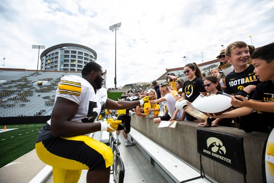 Iowa defensive tackle Daviyon Nixon signs autographs for young fans during a Hawkeyes football Kids Day scrimmage, Saturday, Aug. 10, 2019, at Kinnick Stadium in Iowa City, Iowa.