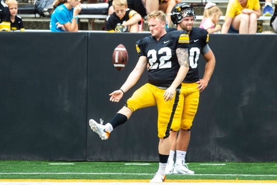 Iowa punter Michael Sleep-Dalton (22) keeps himself entertained on the sideline with teammate Caleb Shudak, right, during a Hawkeyes football Kids Day scrimmage, Saturday, Aug. 10, 2019, at Kinnick Stadium in Iowa City, Iowa.