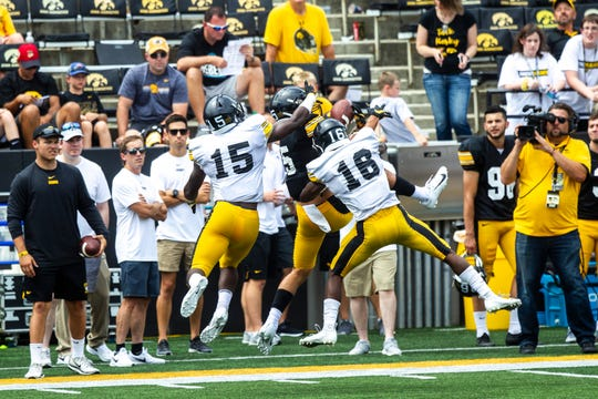 Iowa wide receiver Oliver Martin (5) pulls down a pass between defensive backs Dallas Craddieth (15) and Terry Roberts (16) during a Hawkeyes football Kids Day scrimmage, Saturday, Aug. 10, 2019, at Kinnick Stadium in Iowa City, Iowa.