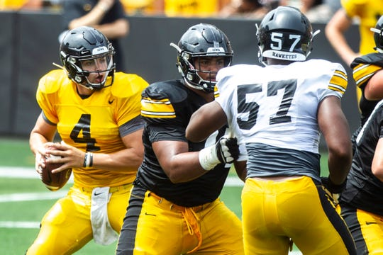 Right tackle Tristan Wirfs, middle, operates against defensive end Chauncey Golston (57) during the Kids Day at Kinnick scrimmage.