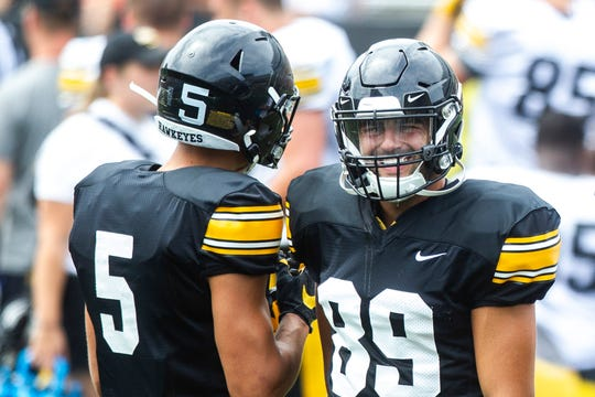 Iowa wide receivers Nico Ragaini, right, and Oliver Martin talk between drills during a Hawkeyes football Kids Day scrimmage, Saturday, Aug. 10, 2019, at Kinnick Stadium in Iowa City, Iowa.