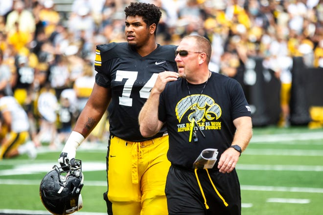 Iowa offensive line coach Tim Polasek (right, with outgoing tackle Tristan Wirfs) now has three offensive linemen committed to the Hawkeyes' 2021 class.