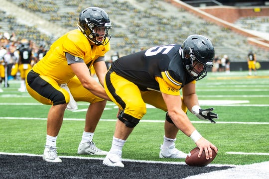 Iowa quarterback Nate Stanley gets a snap from center Tyler Linderbaum while they warm up during a Hawkeyes football Kids Day scrimmage, Saturday, Aug. 10, 2019, at Kinnick Stadium in Iowa City, Iowa.