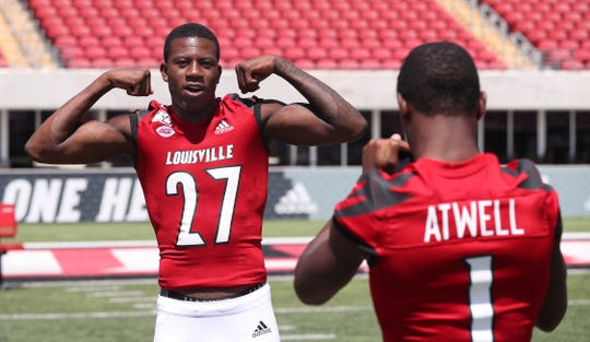 U of L football's Chatarius Atwell (1), right, shoots smartphone photos of teammate Anthony Johnson (27) during media day at Cardinal Stadium.  The Cardinals hope to rebound from a disappointing season last year. Aug. 10, 2019