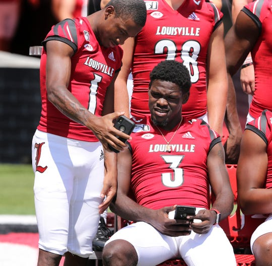 U of L's Chatarius Atwell (1) shares a photo with teammate Malik Cunningham (3) during media day at Cardinal Stadium.  The Cardinals hope to rebound from a disapointing season last year. Aug. 10, 2019