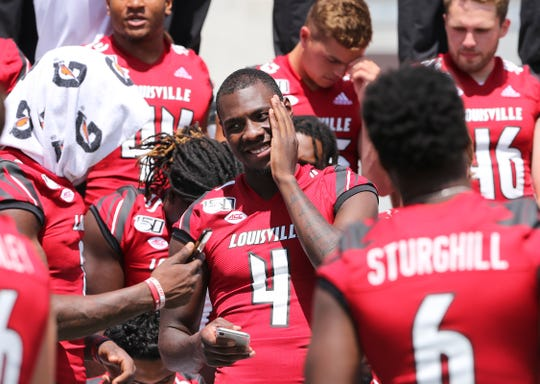 U of L QB Jawon Pass (4) jokes with teammates before posing for a team photo during media day at Cardinal Stadium.  The Cardinals hope to rebound from a disapointing season last year.Aug. 10, 2019