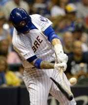 The Brewers' Yasmani Grandal breaks his bat as he grounds out during the fourth inning.