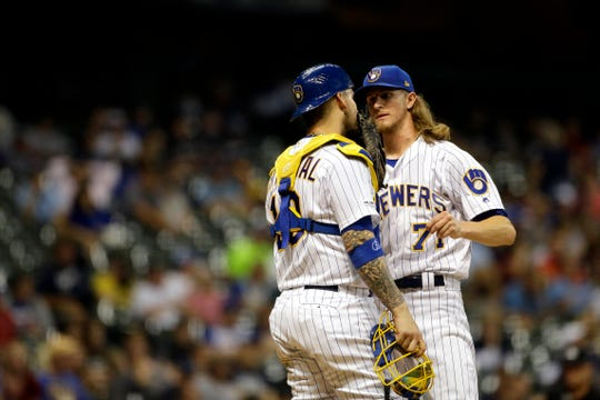 Brewers reliever Josh Hader talks with catcher Yasmani Grandal during the ninth inning Friday night.