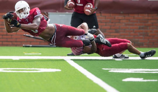 Troy wide receiver Khalil McClain (6) dives for extra yardage as defender Reddy Steward (18) defends as Troy University holds a football scrimmage on campus in Troy, Ala., on Saturday August 10, 2019.