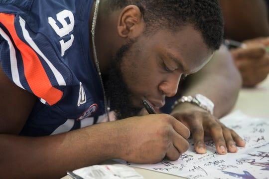Auburn defensive lineman Nick Coe (91) signs autographs during the Auburn Fan Day at the Auburn Athletics Complex in Auburn, Ala., on Saturday, Aug. 10, 2019.