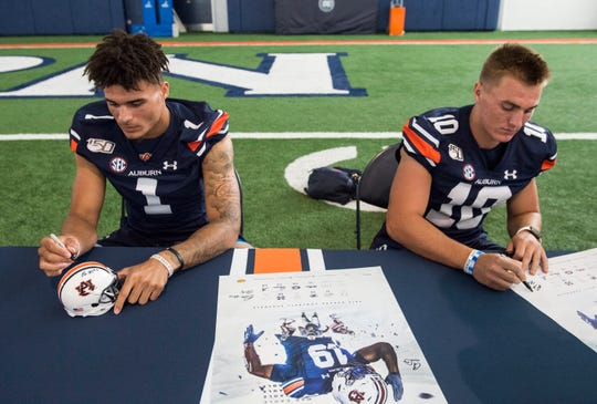 Auburn quarterback's Joey Gatewood (1) and Bo Nix (10) sign autographs during the Auburn Fan Day at the Auburn Athletics Complex in Auburn, Ala., on Saturday, Aug. 10, 2019.