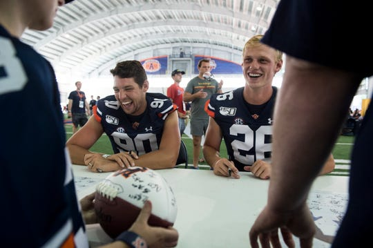 Auburn punter Arryn Siposs (90) and Kicker Anders Carlson (26) sign autographs during the Auburn Fan Day at the Auburn Athletics Complex in Auburn, Ala., on Saturday, Aug. 10, 2019.