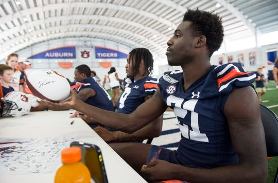 Auburn defensive back Smoke Monday (21) signs autographs during the Auburn Fan Day at the Auburn Athletics Complex in Auburn, Ala., on Saturday, Aug. 10, 2019.