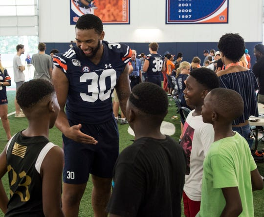 Auburn linebacker Michael Harris (30) jokes with some young fans during the Auburn Fan Day at the Auburn Athletics Complex in Auburn, Ala., on Saturday, Aug. 10, 2019.