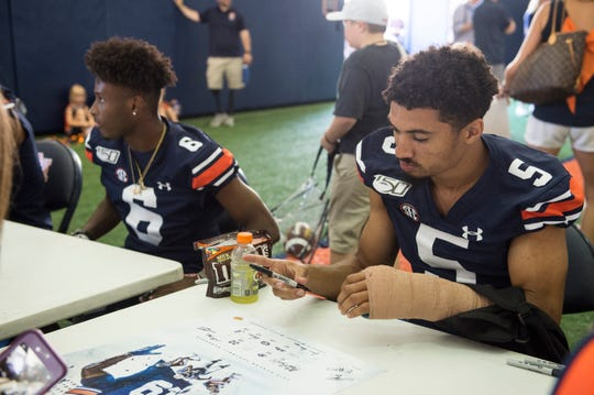 Auburn wide receiver Anthony Schwartz (5) signs autographs in a cast during the Auburn Fan Day at the Auburn Athletics Complex in Auburn, Ala., on Saturday, Aug. 10, 2019.