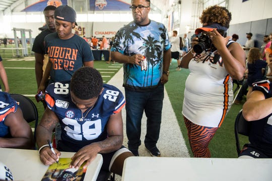 Pamela Whitlow Holloway, right, takes a picture of her son, Auburn running back JaTarvious Whitlow (28), during Fan Day at the Auburn Athletics Complex in Auburn, Ala., on Saturday, Aug. 10, 2019.