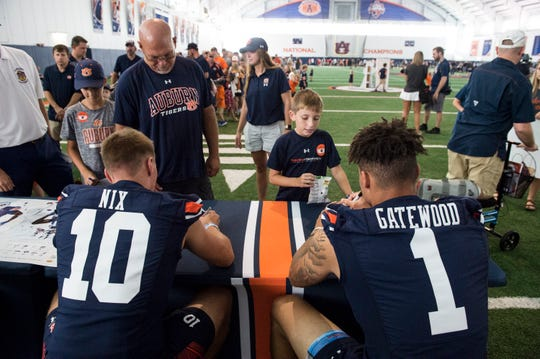 Auburn quarterbacks Bo Nix (10) and Joey Gatewood (1) sign autographs during the Auburn Fan Day at the Auburn Athletics Complex in Auburn, Ala., on Saturday, Aug. 10, 2019.