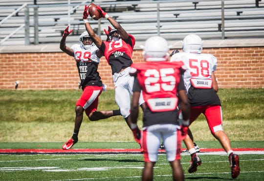 FILE -- Ball State players battle for a ball during a scrimmage at Scheummann Stadium on Aug. 10, 2019. The Cardinals face off against IU on Saturday in their season opener.