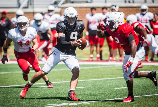 FILE -- Ball State quarterback Drew Plitt prepares to hand off the ball to his running back during a scrimmage during fall camp. The Cardinals face off against IU in their season opener on Aug. 31.