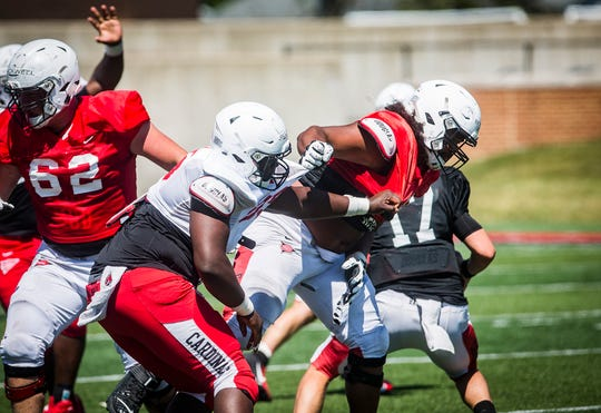 Ball State's Emeka Jillani (left) powers through the offensive line during the team's scrimmage at Scheumann Stadium Saturday.