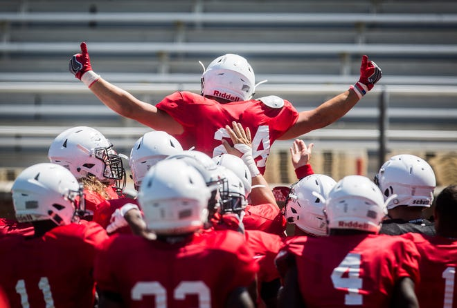 FILE -- Ball State football players celebrate during a scrimmage at Scheummann Stadium on Aug. 10, 2019. The Cardinals face off against IU in their season opener on Aug. 31.