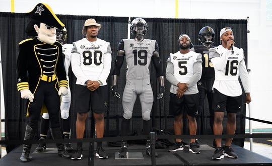 Vanderbilt tight end Jared Pinkney (80), running back Ke'Shawn Vaughn (5) and wide receiver Kalija Lipscomb (16) unveil a new uniform during Dore Jam at Vanderbilt Saturday, Aug. 10, 2019 in Nashville, Tenn.