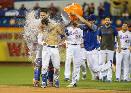 Aug 9, 2019; New York City, NY, USA; New York Mets center fielder Michael Conforto (30) is doused with water  after hitting a walk off RBI single to beat the Washington Nationals 7-6 at Citi Field.