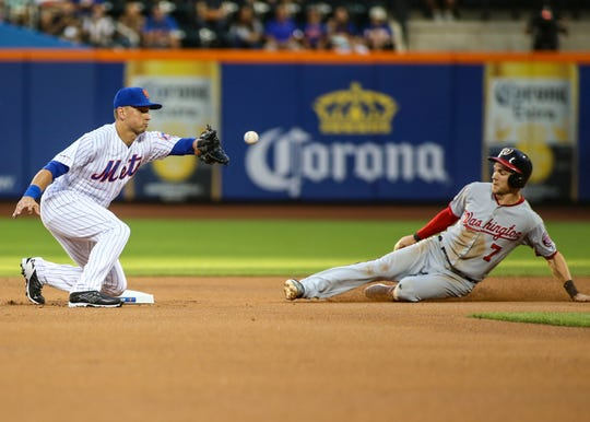 Washington Nationals shortstop Trea Turner (7) avoids the tag of New York Mets second baseman Joe Panik (2) while stealing second base in the first inning at Citi Field.