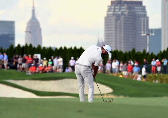 Aug 9, 2019; Jersey City, NJ, USA; Dustin Johnson hits his approach shot to the 18th green during the second round of The Northern Trust golf tournament at Liberty National Golf Course.