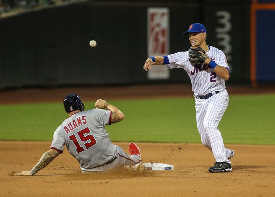 Washington Nationals first baseman Matt Adams (15) tries to break up a double play attempt by New York Mets second baseman Joe Panik (2) in the fourth inning at Citi Field.