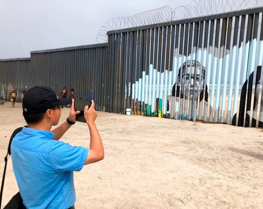 Visitors view a new mural displayed on the Mexican side of a border wall in Tijuana, Mexico, Friday, Aug. 9, 2019. The mural shows faces of people deported from the U.S. with barcodes that activate first-person narratives on visitors' phones. Lizbeth De La Cruz Santana conceived the interactive mural in Tijuana as part of doctoral dissertation at the University of California, Davis. (AP Photo/Elliot Spagat)