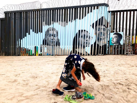A girl stands near a new mural which has been painted on the Mexican side of a border wall in Tijuana, Mexico, Friday, Aug. 9, 2019. The mural shows faces of people deported from the U.S. with barcodes that activate first-person narratives on visitors' phones. Lizbeth De La Cruz Santana conceived the interactive mural in Tijuana as part of doctoral dissertation at the University of California, Davis. (AP Photo/Elliot Spagat)