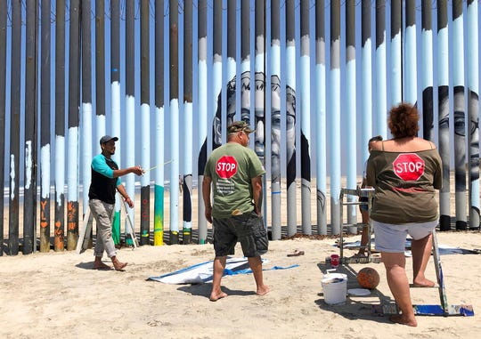 Muralist Mauro Carrera, far left, directs painters working on a new mural on the Mexican side of a border wall in Tijuana, Mexico, Friday, Aug. 9, 2019. The mural shows faces of people deported from the U.S. with barcodes that activate first-person narratives on visitors' phones. Lizbeth De La Cruz Santana conceived the interactive mural in Tijuana as part of doctoral dissertation at the University of California, Davis.  (AP Photo/Elliot Spagat)