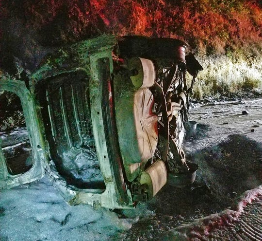 This Aug. 3, 2019 photo from the Hoopa Fire Department shows a Humboldt County Sheriff's Department patrol car after it was struck by a falling bear and then hit an embankment, rolled onto its side and burst into flames, near Hoopa, Calif., in Northern California. The deputy managed to escape without serious injury. (Rod Mendes/Hoopa Fire Department via AP)