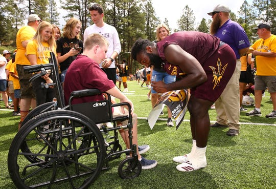 Arizona State Sun Devils running back Eno Benjamin (3) signs his autograph for Creed Nelson from Queen Creek, Ariz., at Camp Tontozona on Aug. 10, 2019 near Kolhs Ranch, Ariz.