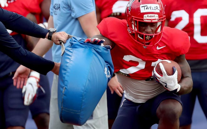 University of Arizona running back J.J. Taylor gets swatted with a pad while fine tuning his technique as the Wildcats work out on day 6 of their pre-season, Tucson, Ariz., August 1, 2019.