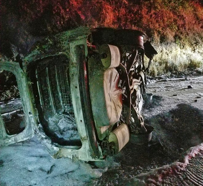 This Aug. 3, 2019, photo from the Hoopa Fire Department shows a Humboldt County Sheriff's Department patrol car after it was struck by a falling bear and then hit an embankment, rolled onto its side and burst into flames, near Hoopa, Calif., in Northern California. The deputy managed to escape without serious injury.