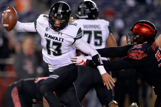 Nov 24, 2018; San Diego, CA, USA; Hawaii Warriors quarterback Cole McDonald (13) is defended by San Diego State Aztecs defensive lineman Chibu Onyeukwu (55) during the second quarter at SDCCU Stadium. Mandatory Credit: Jake Roth-USA TODAY Sports