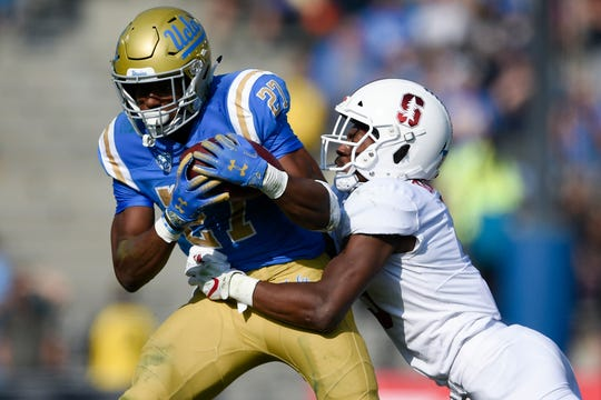 Nov 24, 2018; Pasadena, CA, USA; UCLA Bruins running back Joshua Kelley (27) runs while Stanford Cardinal saftey Frank Buncom (5) defends during the first half at Rose Bowl. Mandatory Credit: Kelvin Kuo-USA TODAY Sports