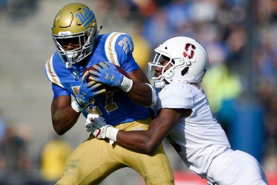 Nov 24, 2018; Pasadena, CA, USA; UCLA Bruins running back Joshua Kelley (27) runs while Stanford Cardinal saftey Frank Buncom (5) defends during the first half at Rose Bowl. Mandatory Credit: Kelvin Kuo-USA TODAY Sports